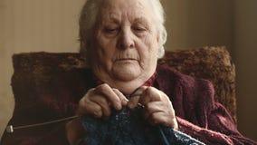 Η ηλικιωμένη γυναίκα κάθεται στο σπίτι και πλέκει τα ενδύματα φιλμ μικρού μήκους