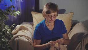 Η ηλικιωμένη γυναίκα κάθεται στο σπίτι και πλέκει το μαντίλι απόθεμα βίντεο