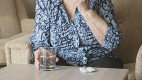 Η ηλικιωμένη γυναίκα παίρνει ένα χάπι και πίνει το νερό φιλμ μικρού μήκους