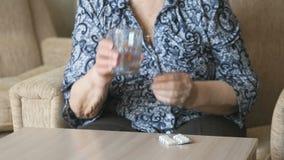 Η ηλικιωμένη γυναίκα παίρνει μια ταμπλέτα και πίνει το νερό φιλμ μικρού μήκους