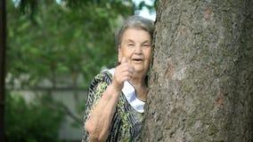 Η ηλικιωμένη γυναίκα παρουσιάζει ότι οι αντίχειρες υπογράφουν επάνω υπαίθρια απόθεμα βίντεο