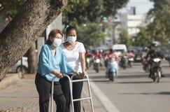 Η ηλικιωμένη γυναίκα που φορά τη μάσκα για προστατεύει την ατμοσφαιρική ρύπανση Στοκ Εικόνες