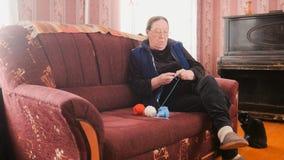 Η ηλικιωμένη γυναίκα στα γυαλιά πλέκει στο σπίτι το μαλλί στοκ φωτογραφίες