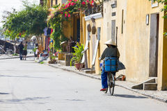 Η ηλικιωμένη γυναίκα στο κωνικό καπέλο οδηγά το ποδήλατο κάτω από την οδό Ho Στοκ Εικόνες