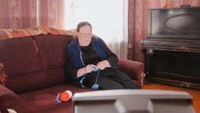 Η ηλικιωμένη κυρία στο σπίτι - ανώτερη τηλεόραση προσοχής γυναικών και πλέκει τις κάλτσες μαλλιού Στοκ Εικόνες