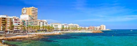 Η ηλιόλουστη μεσογειακή παραλία, τουρίστες χαλαρώνει στη θερμή ακτή της θάλασσας ο Στοκ φωτογραφία με δικαίωμα ελεύθερης χρήσης