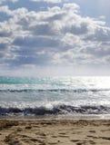 Η θάλασσα, με τα κύματα στο υπόβαθρο του μπλε ουρανού και των σύννεφων Στοκ Εικόνα