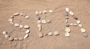 Η θάλασσα λέξης των πετρών στην άμμο, όμορφο υπόβαθρο Στοκ εικόνα με δικαίωμα ελεύθερης χρήσης