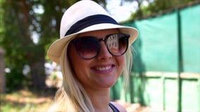 Η θαυμάσια χαμογελώντας γυναίκα με ένα καλό βλέμμα και φυσικός αποτελεί την εξέταση τη κάμερα και τον αέρα που κινεί την τρίχα τη φιλμ μικρού μήκους