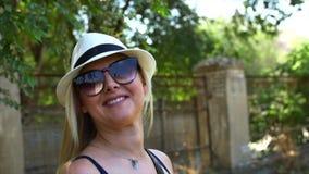 Η θαυμάσια χαμογελώντας γυναίκα με ένα καλό βλέμμα και φυσικός αποτελεί την εξέταση τη κάμερα και τον αέρα που κινεί την τρίχα τη απόθεμα βίντεο