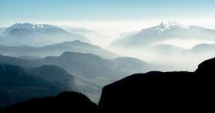 Η θεαματική άποψη του βουνού κυμαίνεται τις σκιαγραφίες και την ομίχλη στις κοιλάδες Στοκ Φωτογραφίες