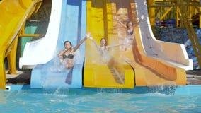 Η θερινή ψυχαγωγία στο aquapark, ολίσθηση φίλων διασκέδασης κάτω στη φωτογραφική διαφάνεια νερού βουτά στη λίμνη με το ράντισμα φιλμ μικρού μήκους