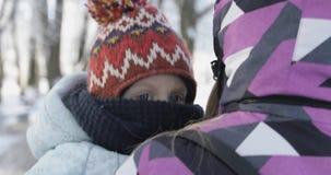 Η θερμά ντυμένη γυναίκα αντέχει στα όπλα της ένα μικρό παιδί στο πάρκο το χειμώνα απόθεμα βίντεο
