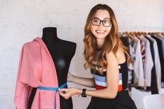 Η θετική νέα γυναίκα ντύνει το σχεδιαστή στο ατελιέ στοκ φωτογραφία με δικαίωμα ελεύθερης χρήσης