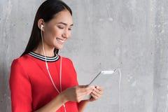 Η θετική νέα γυναίκα χρησιμοποιεί την έξυπνη συσκευή Στοκ Εικόνες