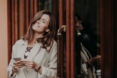 Η θετική νέα γυναίκα brunette με το οδοντωτό χαμόγελο, φορά smartwatch, ντυμένος στο κομψό σακάκι, σύγχρονο τηλέφωνο κυττάρων χρή στοκ εικόνες