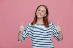 Η θετική νέα Ευρωπαία γυναίκα με την κοκκινωπή τρίχα κρατά δύο αντίχειρες αυξημένους, γέρνει το κεφάλι, που ντύνεται στα ριγωτά ε στοκ φωτογραφία