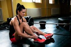 Η θηλυκή κατάλληλη στήριξη κοριτσιών και τα πάνινα παπούτσια δοχείων και προετοιμάζονται για την άσκηση Στοκ Εικόνα