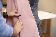 Η θηλυκή μοδίστρα συνδέει το ύφασμα με το μανεκέν με τις βελόνες δημιουργία του σχεδίου φορεμάτων Έννοια βιομηχανίας ραφτών στοκ εικόνες με δικαίωμα ελεύθερης χρήσης