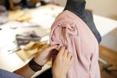 Η θηλυκή μοδίστρα συνδέει το ύφασμα με το μανεκέν με τις βελόνες δημιουργία του σχεδίου φορεμάτων Έννοια βιομηχανίας ραφτών στοκ εικόνα