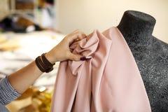 Η θηλυκή μοδίστρα συνδέει το ύφασμα με το μανεκέν με τις βελόνες δημιουργία του σχεδίου φορεμάτων Έννοια βιομηχανίας ραφτών στοκ φωτογραφίες με δικαίωμα ελεύθερης χρήσης