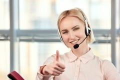 Η θηλυκή ξανθή ώριμη παρουσίαση χειριστών τηλεφωνικών κέντρων φυλλομετρεί επάνω Στοκ Εικόνες