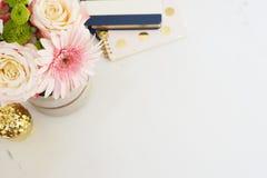Η θηλυκή έννοια εργασιακών χώρων στο επίπεδο βάζει το ύφος με, λουλούδια, το χρυσό ανανά, σημειωματάρια στο άσπρο μαρμάρινο υπόβα στοκ εικόνες με δικαίωμα ελεύθερης χρήσης