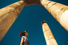 Η θηλυκή στάση τουριστών μεταξύ των στηλών που εξερευνούν το ναό Hercules παραμένει στο λόφο ακροπόλεων του Αμμάν αρχαίες καταστρ Στοκ Φωτογραφίες