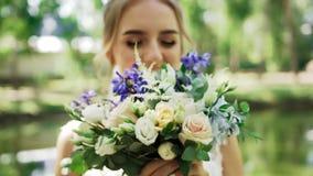 Η θολωμένη νέα νύφη γυναικών χαίρεται το κράτημα της γαμήλιας ανθοδέσμης της φιλμ μικρού μήκους