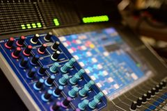 Η θολωμένη γενική φωτογραφία του αναμίκτη και του εξισωτή Soundboard ραδιοφωνικής μετάδοσης μουσικής συναυλίας με τα εξογκώματα κ στοκ εικόνα με δικαίωμα ελεύθερης χρήσης