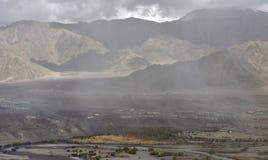 Η θύελλα και η ομίχλη σκόνης στα υψηλά βουνά της κοιλάδας, ο αέρας αυξάνουν τα σύννεφα της σκόνης, οι περιλήψεις των βουνών χάνον Στοκ Φωτογραφίες