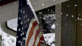 Η θύελλα καλύπτει αργά τη αμερικανική σημαία στο χιόνι φιλμ μικρού μήκους