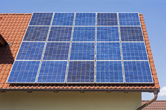 Ηλιακά πλαίσια στην κόκκινη στέγη σπιτιών Υπόβαθρο ηλιακής ενέργειας Στοκ Φωτογραφία