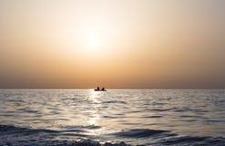 Ηλιακή πορεία στη θάλασσα, ψαράδες σε μια βάρκα στοκ εικόνες