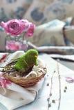 Η διακόσμηση Πάσχας - πουλί σε μια φωλιά με τη δαντέλλα, ρόδινα τριαντάφυλλα και Στοκ φωτογραφία με δικαίωμα ελεύθερης χρήσης