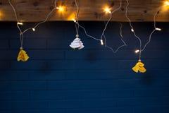 Η διακόσμηση Χριστουγέννων ανάβει κίτρινο άσπρο ξύλο τουβλότοιχος δέντρων το μπλε Στοκ εικόνα με δικαίωμα ελεύθερης χρήσης
