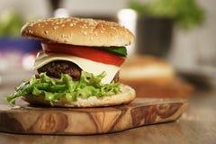 Η διασκέδαση έκανε φρέσκο burger με το μαρμάρινα βόειο κρέας, το τυρί και τα λαχανικά στον πίνακα ελιών Στοκ φωτογραφίες με δικαίωμα ελεύθερης χρήσης