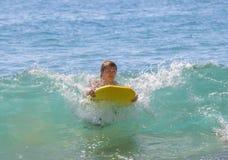 η διασκέδαση αγοριών έχει τα κύματα σερφ στοκ φωτογραφία με δικαίωμα ελεύθερης χρήσης