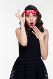 Η διασκέδαση κατέπληξε τη σγουρή νέα γυναίκα στα κόκκινα διαμορφωμένα καρδιά γυαλιά Στοκ Φωτογραφίες