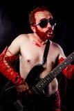 Η διασκέδαση, κιθαρίστας με την ηλεκτρική κιθάρα μαύρη, φορώντας το πρόσωπο χρωματίζει Στοκ φωτογραφία με δικαίωμα ελεύθερης χρήσης