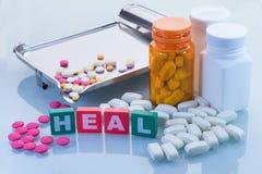 Η ιατρική έννοια με θεραπεύει το κείμενο και τα χάπια με το υπόβαθρο μπουκαλιών Στοκ Φωτογραφίες