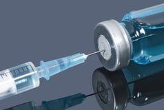 Η ιατρική βελόνα στο φιαλίδιο με το μπλε υγρό στο σκοτεινό υπόβαθρο Στοκ Φωτογραφίες