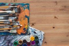 Η διαφορετική συλλογή πινέλων μεγέθους σε μια παλαιά παλέτα με το ελαιόχρωμα χρωματίζει το μίγμα και ένα σύνολο γκουας, τοπ εικόν στοκ φωτογραφία με δικαίωμα ελεύθερης χρήσης