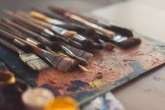Η διαφορετική συλλογή πινέλων μεγέθους σε μια παλαιά παλέτα με το ελαιόχρωμα χρωματίζει το μίγμα και ένα σύνολο γκουας στοκ εικόνα με δικαίωμα ελεύθερης χρήσης