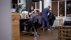 Η διαδικασία της κοπής τρίχας στο barbershop, διάφοροι κομμωτές κάνει τα μοντέρνα και μοντέρνα hairstyles στα άτομα ` s απόθεμα βίντεο