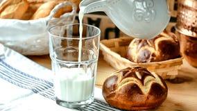 Η διαδικασία το γάλα σε ένα γυαλί από τη στάμνα, φρέσκια αλυσίβα κυλά σε ένα ψάθινο καλάθι απόθεμα βίντεο