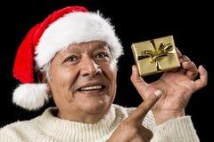Ηλικίας άτομο με το εμφατικό βλέμμα και το χρυσό δώρο στοκ φωτογραφίες