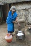 Ηλικίας γυναίκα που παίρνει το πόσιμο νερό από τη δημόσια βρύση Στοκ Φωτογραφία