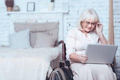 Ηλικίας με ειδικές ανάγκες γυναίκα που χρησιμοποιεί τη συσκευή στο σπίτι Στοκ Εικόνες