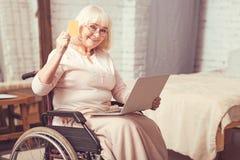 Ηλικίας με ειδικές ανάγκες κυρία που χρησιμοποιεί τη σύγχρονη συσκευή στο σπίτι Στοκ Φωτογραφία
